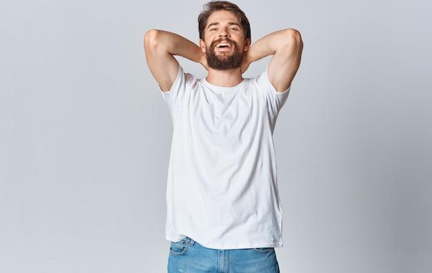 Un homme dans un t-shirt blanc sur un espace léger fait des gestes avec ses mains vue recadrée de jeans copier