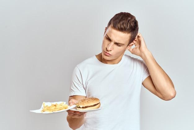 Un homme dans un t-shirt blanc avec hamburger de restauration rapide dans ses mains