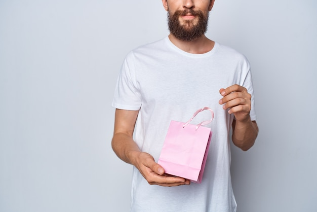 Un homme dans un t-shirt blanc tenant un cadeau de vacances de paquet rose
