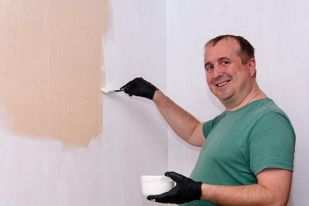 Un homme dans un t-shirt vert peint le mur intérieur d'un appartement