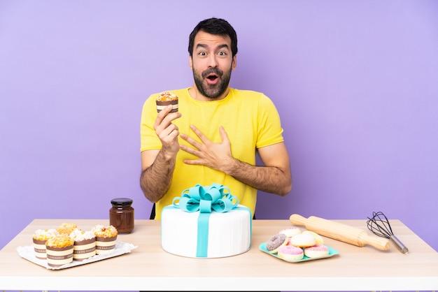 Homme dans une table avec un gros gâteau sur backgroun violet