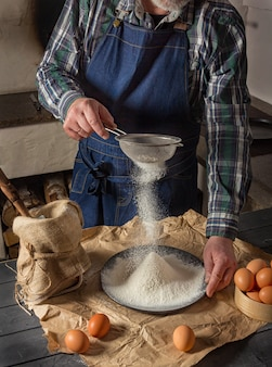 Homme dans un tablier en denim tamiser la farine