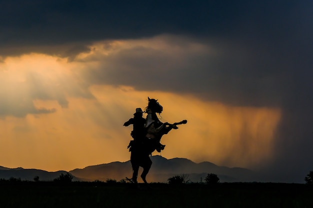 Un homme dans une tenue de cow-boy avec son cheval