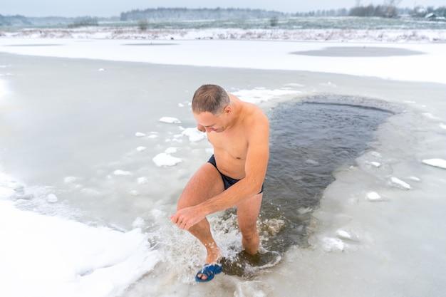 Homme dans un trou de glace à l'extérieur