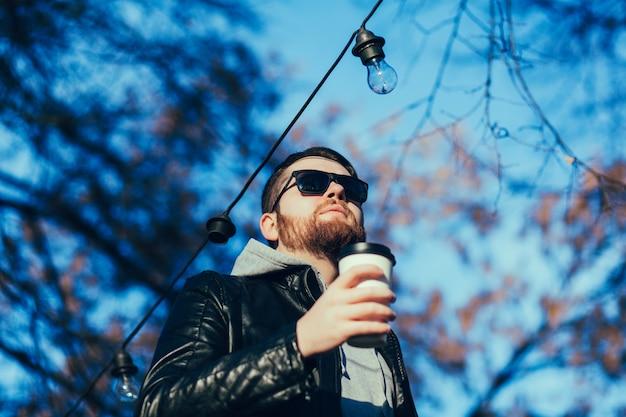 Homme dans une veste en cuir avec café