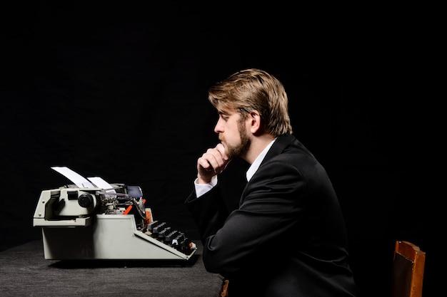 Homme dans une veste noire en tapant sur une machine à écrire