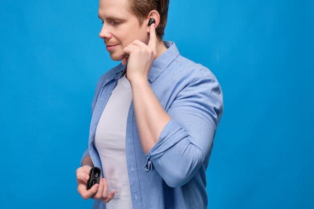 Homme dans des vêtements décontractés sur bleu change la chanson en appuyant sur l'écouteur sans fil dans son oreille.