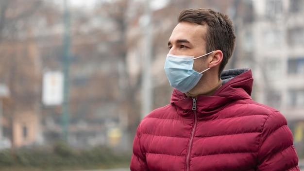Homme dans la ville portant un masque médical