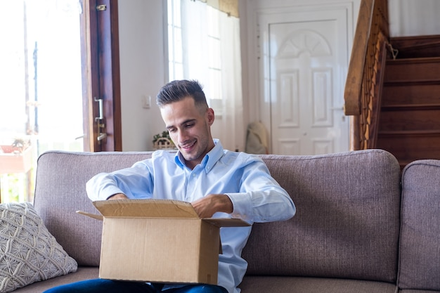 Homme déballant le paquet d'ouverture de la boîte de livraison à la maison. heureux jeune homme regardant une boîte en carton assis sur un canapé dans le salon à la maison. homme vérifiant des trucs livrés à la maison.