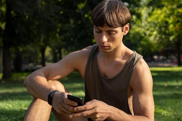 Homme en débardeur regardant smartphone tout en travaillant à l'extérieur