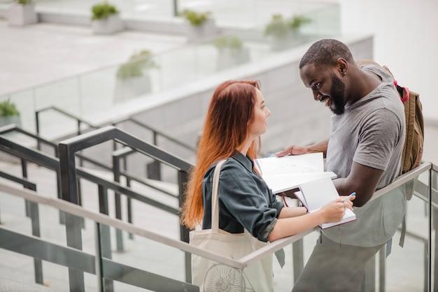 Homme debout et aidant femme avec des docs
