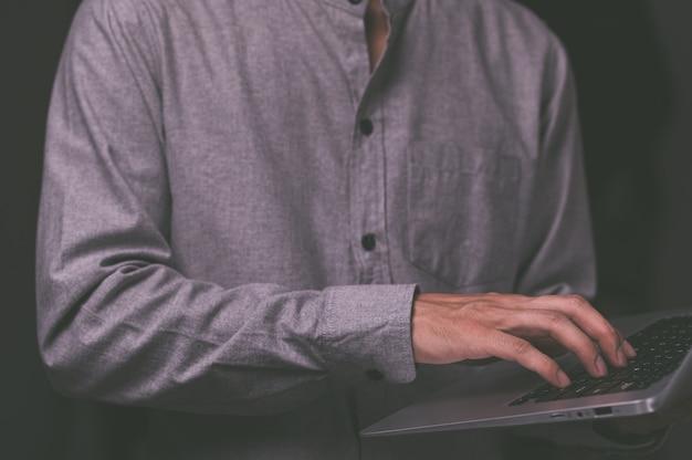 Un homme debout à l'aide d'un ordinateur portable