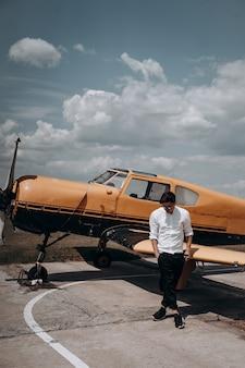 Un homme debout sur l'arrière-plan d'un petit avion monomoteur.