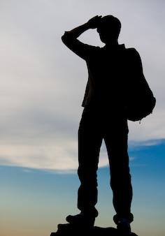 Homme debout au sommet d'un rocher se découpant sur un ciel du soir alors qu'il regarde au loin avec sa main levée sur son front