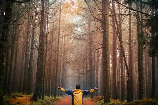 Homme debout à bras ouverts dans la nature