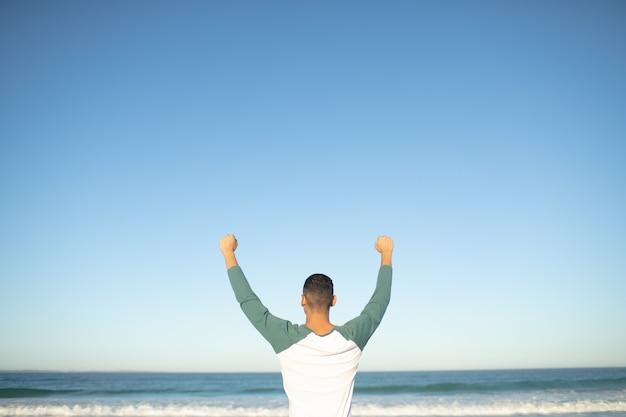 Homme debout avec les bras sur la plage