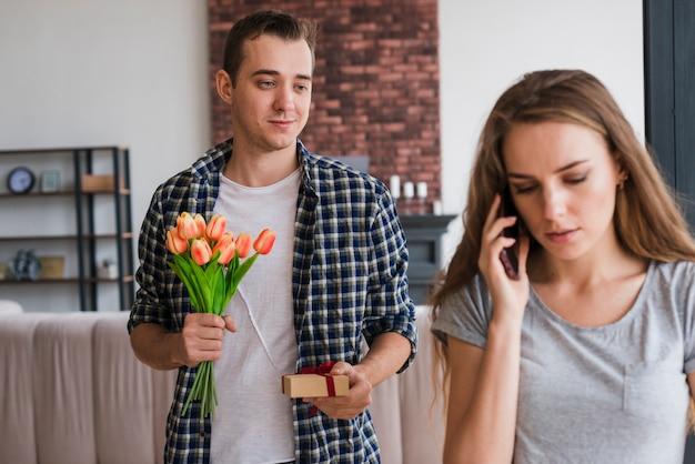 Homme debout avec des cadeaux derrière une femme