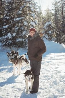 Homme debout avec des chiens husky sibériens