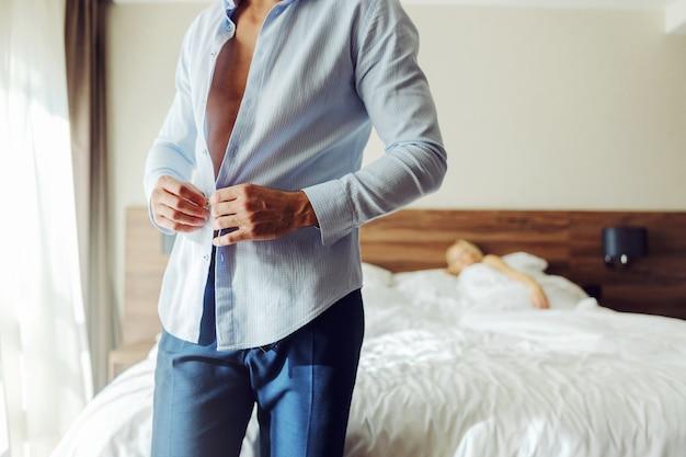 Homme debout à côté d'un lit dans une chambre d'hôtel et boutonnant une chemise pendant que son amant est allongé dans un lit.