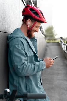 Homme debout à côté de son scooter tout en vérifiant son téléphone
