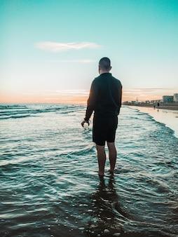 Homme debout dans l'eau de mer avec verre à la main