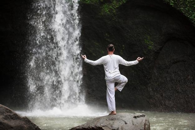 Homme debout dans la méditation yoga sur rocher à cascade dans les tropiques de bali
