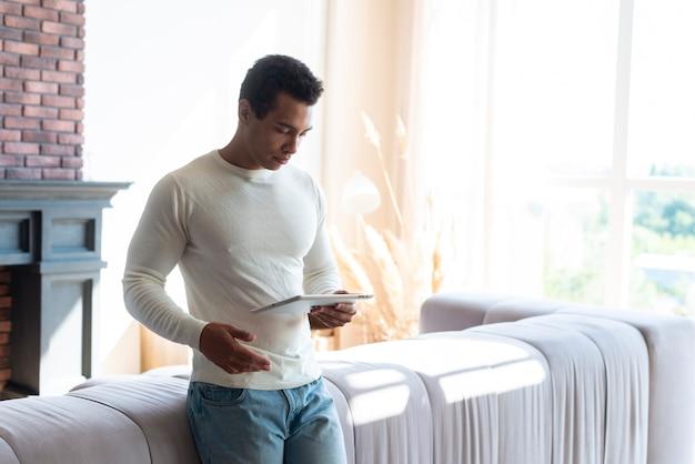 Homme debout dans la vie et tenant la tablette