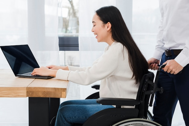 Homme debout derrière la femme handicapée souriante assise sur un fauteuil roulant à l'aide d'un ordinateur portable