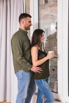 Homme debout derrière sa copine tenant une tasse de café à la main