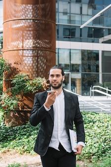 Homme debout devant le bâtiment tenant un téléphone portable à la main et parlant au haut-parleur