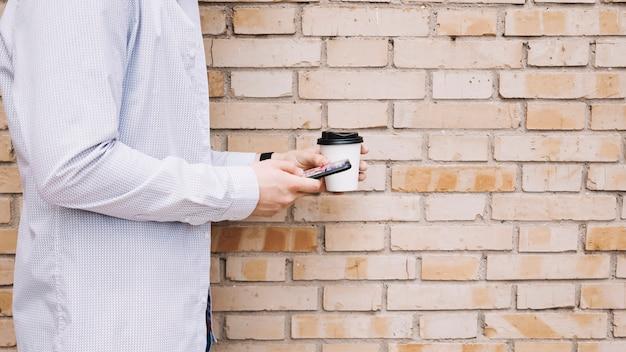 Homme, debout, devant, brique, mur, tasse café, et, téléphone portable, tenue, dans, main