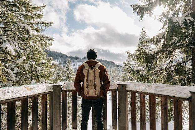 Homme debout devant des clôtures en bois entourées de collines et de forêts couvertes de neige