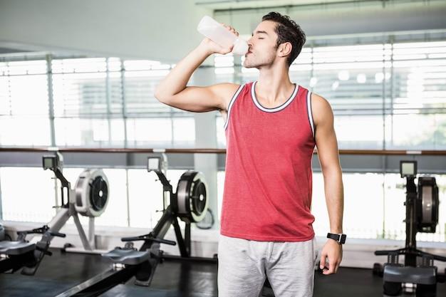 Homme debout, eau potable dans la salle de sport