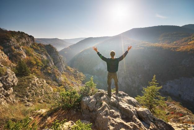 Homme debout sur la falaise en montagne.