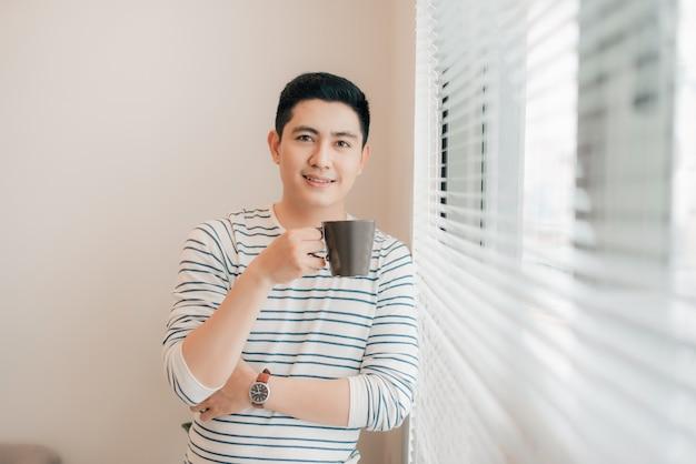 Homme debout à la fenêtre et boire le premier café du matin