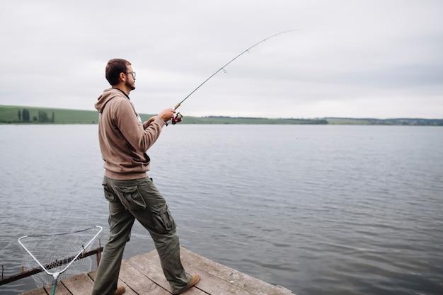 Homme debout sur la jetée de pêche dans le lac