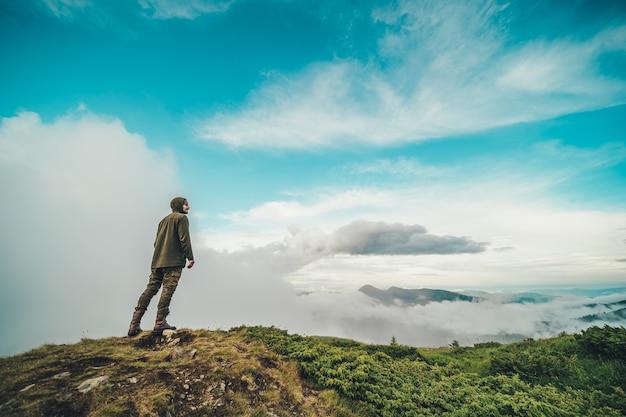 L'homme debout sur la montagne sur un beau fond de nuages
