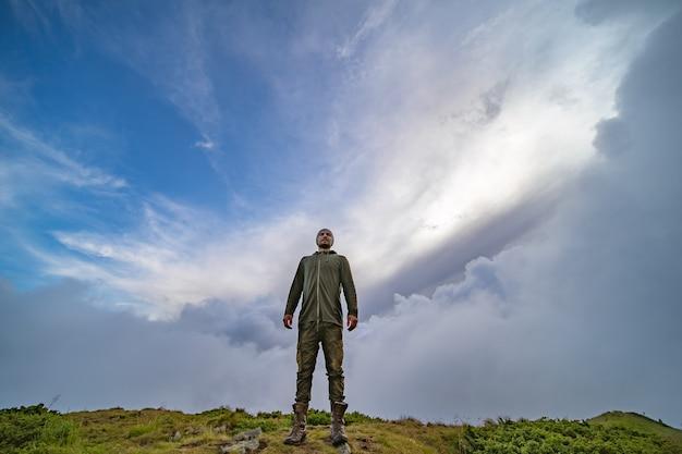 L'homme debout sur la montagne sur un fond de ciel nuageux