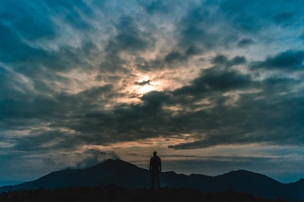 L'homme debout sur la montagne sur fond de nuage