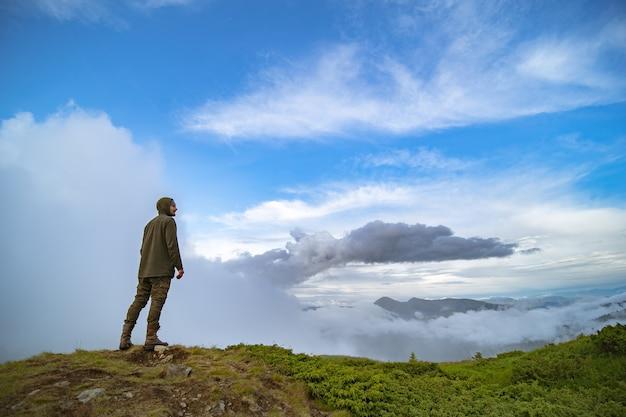 L'homme debout sur la montagne sur fond de nuages blancs