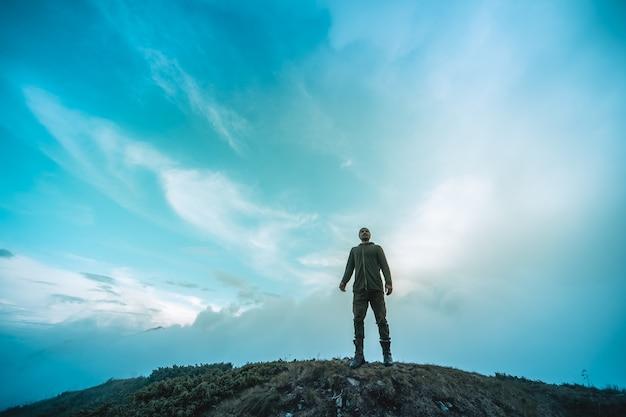 L'homme debout sur la montagne sur un fond de nuages pittoresque