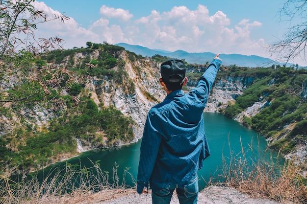 Homme debout sur la montagne rocheuse en vue du lac