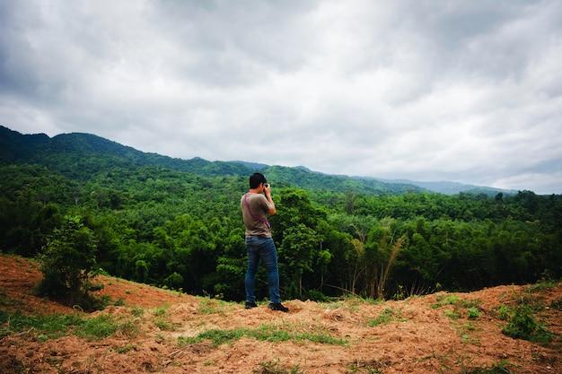 Homme debout sur la montagne utiliser la caméra prendre vue du paysage