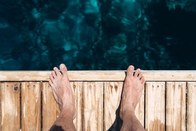 Homme debout pieds nus sur la jetée au bord de la mer se bouchent