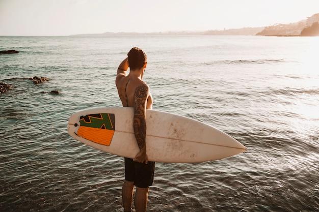 Homme debout avec planche de surf en mer