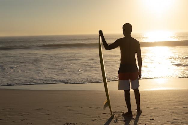 Homme debout avec planche de surf sur la plage