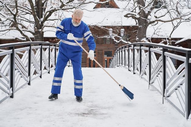 Homme debout sur le pont et enlever la neige en hiver