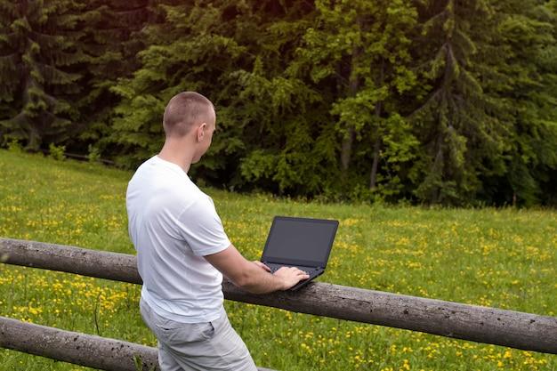 Homme debout près de la clôture en bois sur le terrain et travaille sur un ordinateur portable près de la forêt de pins