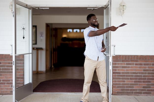 Homme debout près de l'église et distribuant des brochures en souriant