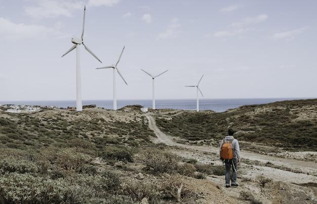 Homme debout près des éoliennes